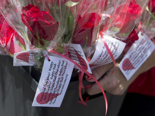 "Elana Wight passed out more than 300 long-stemmed roses to cancer patients and staff at Arizona Oncology for ""Red Thursday."""