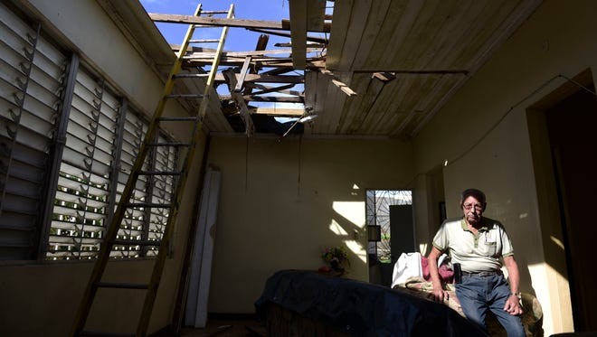 In this Nov. 15, 2017 photo, Edgardo de León sits in his living room with a hole in the ceiling caused by the whip of hurricane Maria, in Cataño, Puerto Rico.   A newly created Florida company with an unproven record won more than $30 million in contracts from the Federal Emergency Management Agency to provide emergency tarps and plastic sheeting for repairs to hurricane victims in Puerto Rico. Bronze Star LLC never delivered those urgently needed supplies, which even months later remain in demand on the island.
