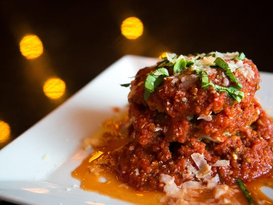The Tower of Power is a stack of panko crusted fried green tomatoes, bleu cheese and jumbo lump crab served with a spicy marinara sauce and a basil garnish.