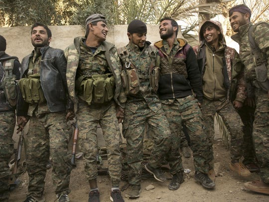 U.S.-backed Syrian Democratic Forces fighters celebrate their territorial gains over Islamic State militants in Baghouz, Syria, on Tuesday. It was a major advance but not the final defeat of the group.