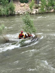 A fire department crew rescues a woman from the Truckee River in downtown Reno on Sunday, June 25, 2017.