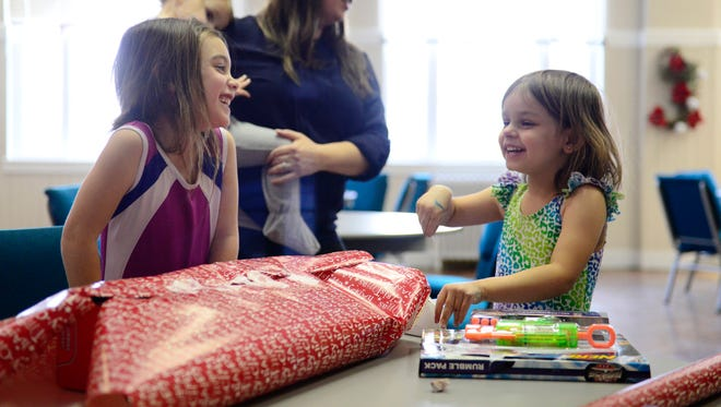 Vivan LaJune, 4, left and Micah Deuel, 4, wrap presents that will be given to children at Ponifex's 14th Annual Christmas Eve Celebration.