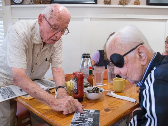 Naples veterans Frank Pagano, left, and Hank Markovich look through old class photos together during a weekly lunch Nov. 4 at Skillets in North Naples. Pagano and Markovich graduated in the same class from Cass Tech High School in Detroit, served in World War II and were both automobile executives. The two hadn't seen each other in about 70 years until they learned from a Naples Daily News article that they were both living in Naples. Markovich, 90, died Wednesday.