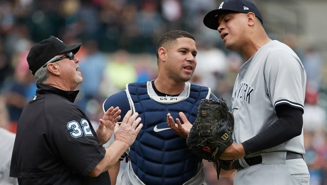 New York Yankees relief pitcher Dellin Betances (68) reacts in front of catcher Gary Sanchez (24) after he is ejected by umpire Dana DeMuth (32) in the seventh inning against the Detroit Tigers at Comerica Park.
