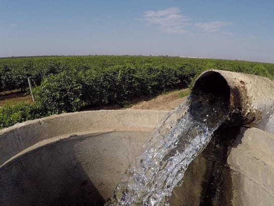 Water flows from a well into a standpipe in California's