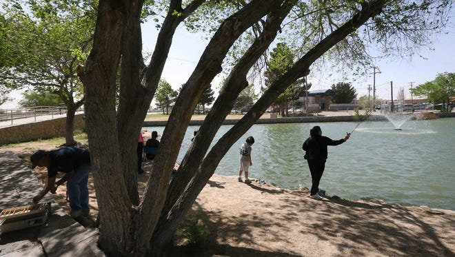 Cathy Espiinosa, right, casts a line into the water as her family held an outing with the Sanchez family Thursday at Ascarate Park.