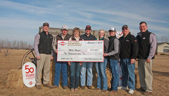 Mike Hayen, of Cogswell, N.D., was presented with a ceremonial check representing $10,000 off the purchase of a KUHN GMD 5251 TC center-pivot disc mower.  Present for the award ceremony were Mike and LaJuana Hayen, their children (Garrett, Bridget and Elliott), Jon Stephenson, Chuck Friedley, and Titan Machinery Sales Representative Wally Radcliffe.