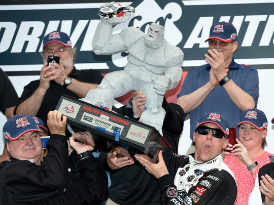 Kevin Harvick, front right, hoists and poses with the trophy in Victory Lane after he won the NASCAR Cup Series auto race, Sunday, May 6, 2018, at Dover International Speedway in Dover.