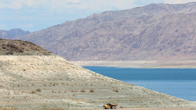 A large truck drives near the receding shoreline at Lake Mead in August 2015. The reservoir is the largest in the country and has been declining dramatically in recent years.