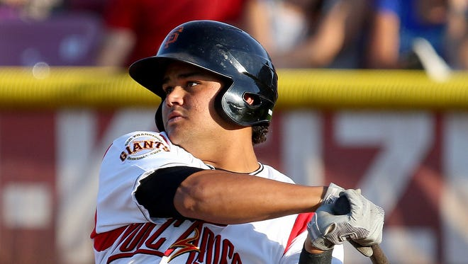 Volcanoes outfielder Julio Pena watches the ball off his bat against Boise at Volcanoes Stadium, on Wednesday, July 15, 2015, in Keizer, Ore.