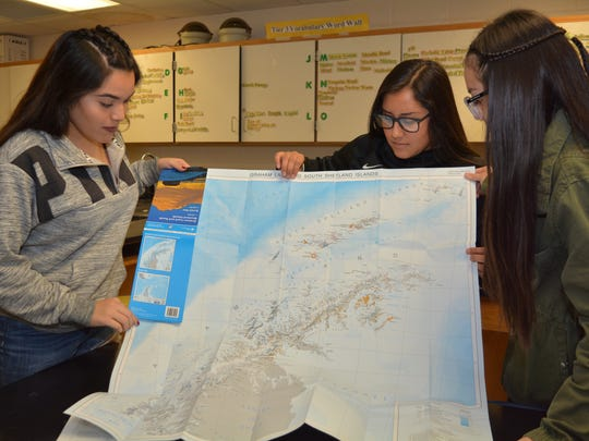 Santa Teresa High students Hannah Castro, left, Paolina Frias, and Annabel Balderas, on Jan. 10, 2018, examine a map of Antarctica. Their teacher, Monica Nuñez, recently spent two weeks visiting the remote continent as part of a National Geographic Grosvenor Fellowship.