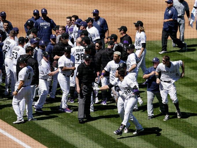 Rockies' Nolan Arenado is restrained by Carlos Gonzalez.