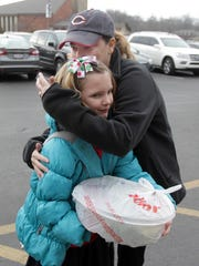 Mollie Pegram hugs her daughter, Riley, 8, as she picks her up from school at Milford Christian Academy. Pegram arrived home Friday from the Cleveland Clinic, where she underwent the surgery and has been treated since mid-November.