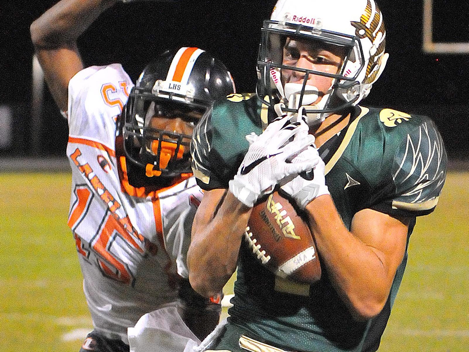 Viera High's Tre Nixon comes down with a nice catch in front of Lakeland's Damarri Mathis for a first down during Friday night's regional finals held at Viera High School Stadium.