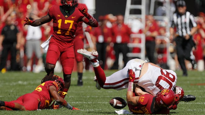 Iowa State defensive back Greg Eisworth, bottom right, tackles Oklahoma tight end Grant Calcaterra, top, right, to force a fumble and a turnover during the first half of an NCAA college football game, Saturday, Sept. 15, 2018, in Ames, Iowa. Iowa State defensive back Richard Bowens (17) recovered the fumble. (AP Photo/Matthew Putney)