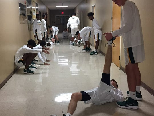 The Calvary basketball team warms up in the hall outside
