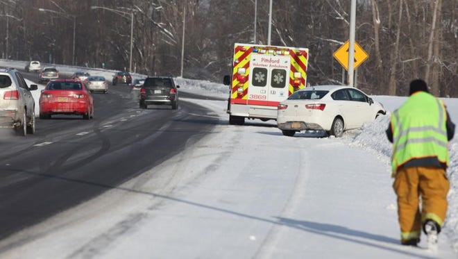 Several cars, including this one near Bushnell's Basin, slid off I-490 Friday morning.