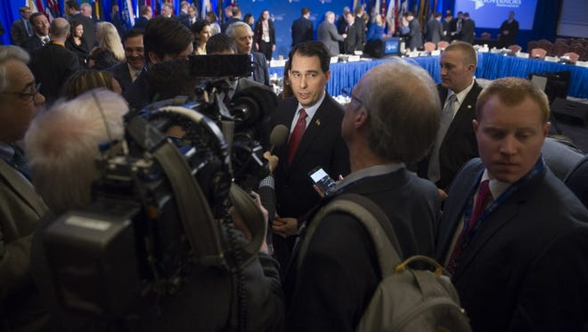 Wisconsin Gov. Scott Walker, center, talks to reporters Saturday at the  National Governors Association conference in Washington.