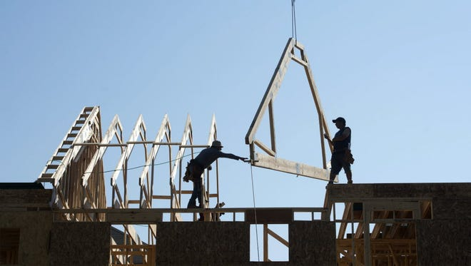 Construction workers build the roof of a new multi-family home in Alexandria, Va.