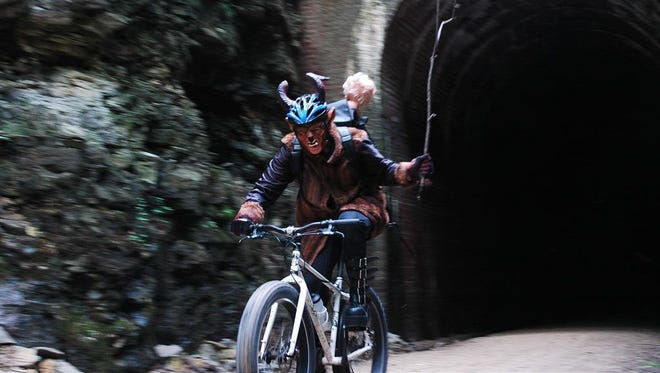 John McNeill rides through the Stewart Tunnel in a Krampus costume. This photo was taken for a contest for Surly bicycles, which has a Krampus model.