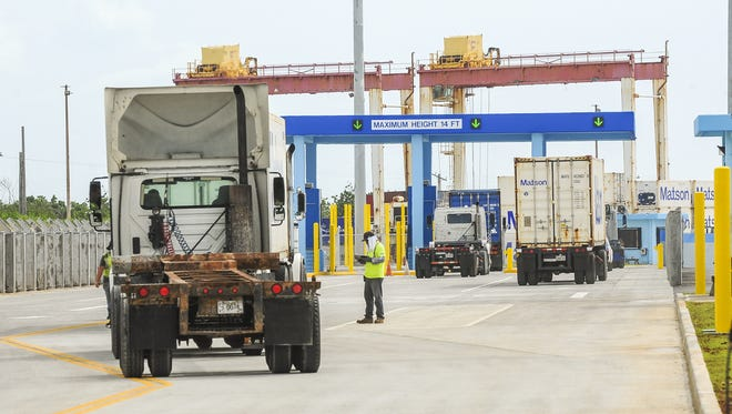 A port worker looks over paperwork as a truck driver checks in at the new terminal gate complex at the Port Authority of Guam on Cabras Island on Monday, Aug. 3, 2015. With the new gate system, the port is able to process more transport vehicles entering the port in less time, resulting in a streamlining of its operations and improving traffic flow because the elimination of trucks backing up on the main road to the facility, said Joanne Brown, PAG general manager.