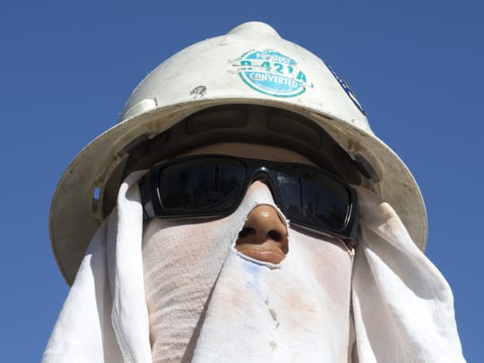 Orlando Jardines protects his face from the sun Monday,