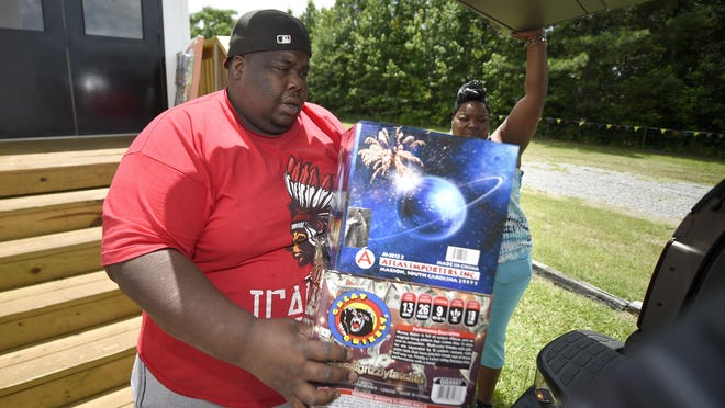 Jermaine Wingfield loads fireworks into his car with the help of Lakisha Gresham at Wacky Wayne's Fire Works in North Augusta, SC., Thursday afternoon June 25, 2020.