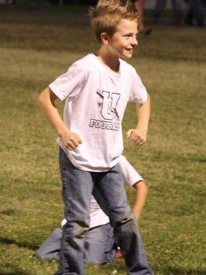 One of the little league team players enjoys his time on the sidelines of the game during Friday's game.