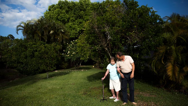 "Tim Winschel helps his mother, Connie Winschel, across the front yard on Friday, May 5, 2017, at Tim's home in North Naples. Connie is our ""Mother of the Year"" winner for her dedication to her family and a life of overcoming incredible challenges and hardships."
