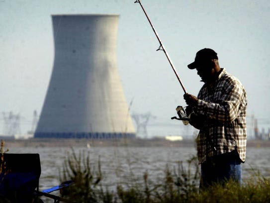 The Hope Creek nuclear plant is seen from across the Delaware River, behind this fisherman.