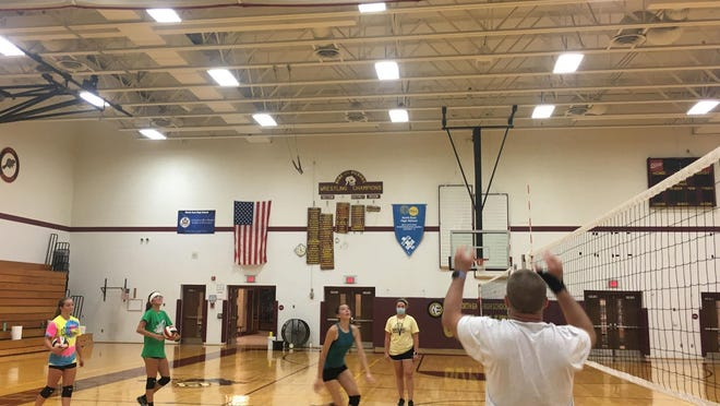 North East girls volleyball coach Bob North, foreground, sets the ball for players during a hitting drill at North East's gym during the opening day of practice. The Grapepickers will host Union City on Thursday night.