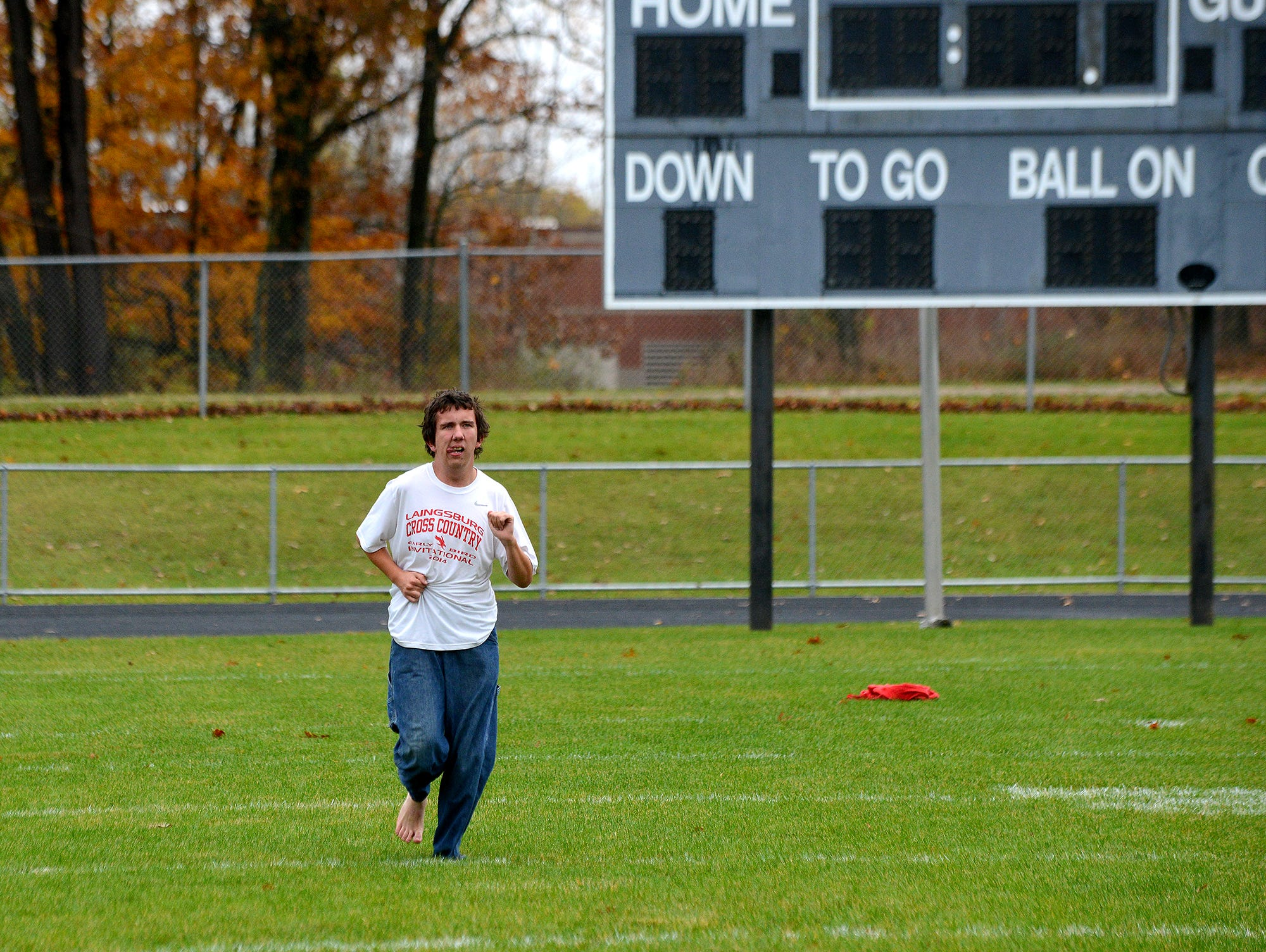 """Ray Latchaw practices with his teammates on the Laingsburg cross country team Wednesday, October 28, 2015 at Laingsburg High School. Latchaw, a junior, is autistic, but runs, he says, to stay healthy and because he enjoys the """"me time"""" he gets. Ray forgot his running gear at home, so he had to run in jeans."""