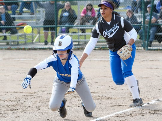 Olympic High third baseman Kaira Cabato tries to make a defensive play against Bremerton's Jordyn Garrity in an April 1 game at Lions Park. Cabato's season ended 10 days later, when she suffered a knee injury during a game against Kingston.