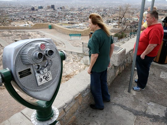 Sherry Hulsey, of Las Cruces, center, looks out at the El Paso-Juárez area while taking family members from Salt Lake City to Murchison Rogers Park along Scenic Drive on Wednesday.