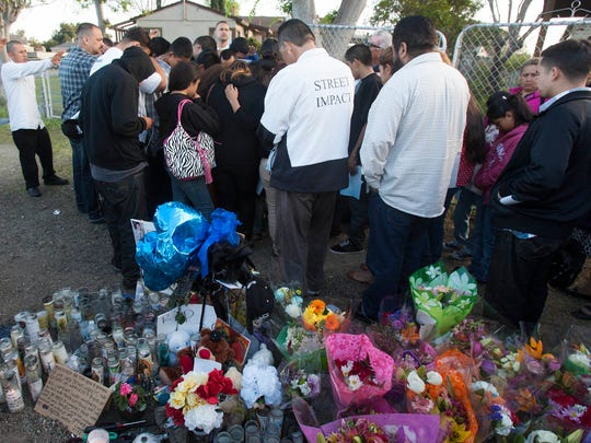 Family members and friends of Josue Lopez gather on March 13, 2013, for a prayer vigil at the place where the 16-year-old was shot a few days before on Stroube Street near Alvarodo Street in El Rio.