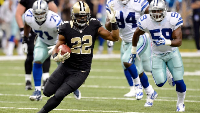 New Orleans Saints running back Mark Ingram (22) carries the ball up the field against the Dallas Cowboys defense.