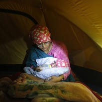 Prabina Mainali, feeds her newly born baby boy - not even a day old - in a makeshift tent situated in open ground from fear of earthquake tremors, in Katmandu, Nepal, Monday, April 27, 2015. A strong magnitude earthquake shook Nepal's capital and the densely populated Kathmandu valley on Saturday devastating the region and leaving tens of thousands shell-shocked and sleeping in streets.