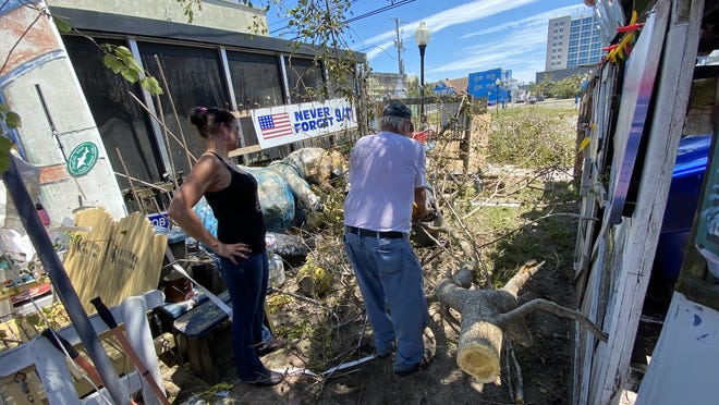 Danny McLaughlin, right, cuts up a fallen tree that dislodged the brick flooring of his popular Carolina Beach bar, The Fat Pelican, during Hurricane Isaias. [HUNTER INGRAM/STARNEWS}