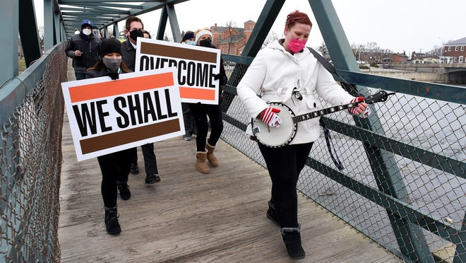 "Donna Hwang of Monroe plays the banjo as she leads the Monroe County Community College Unity Peace March in honor of Dr. Martin Luther King Jr. Tuesday afternoon. Erika Hunt, human resources assistant at MCCC holds the ""We Shall"" sign, while Scott Behrens, vice president of  enrollment management and student success and Bonnie Weber of Dundee hold the ""Overcome"" sign as the group crosses the Dr. Martin Luther King Jr. pedestrian bridge."