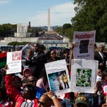 People cheer during a rally to mark the 20th anniversary of the Million Man March, on Capitol Hill, on Saturday, Oct. 10, 2015, in Washington. Waving flags, carrying signs and listening to speeches and songs, the crowd gathered at the U.S. Capitol and spread down the Mall under on a sunny and breezy fall day.  (AP Photo/Evan Vucci)