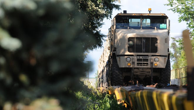 Oshkosh Corp. vehicles sit on a train behind the homes of Allerton Drive residents in this August 2013 file photo.