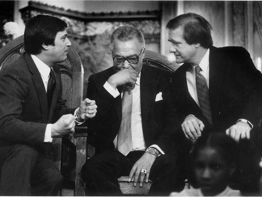 Democratic gubernatorial candidate James Blanchard (left) confers with U.S. Senator Donald Riegle as Mayor Coleman Young (center) ponders at St. James Missionary Baptist Church in Detroit.  Young was hosting a Democratic candidates tour of four Detroit church in preparation for the November election.