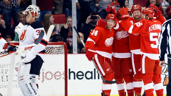 Detroit Red Wings left wing Johan Franzen receives congratulations from teammates after scoring on New Jersey Devils goalie Cory Schneider at Joe Louis Arena.