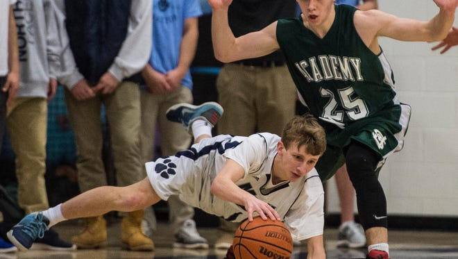 St. Johnsbury Academy's #25 Alex Carlisle trips up MMU's #2 Trent LaBounty during their boys basketball match up in Jericho Friday night, Jan. 27, 2017. Battling back from a deficit much of the game, St. J would pull ahead in the final seconds after a tie that forced over time. But MMU's LaBounty shut the door with a stunning three-point shot in the final seconds to win 58-56.