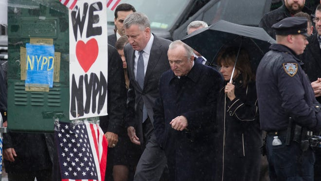 New York City Mayor Bill de Blasio, center left, New York Police Department Commissioner Bill Bratton, center right, and Rikki Klieman, Bratton's wife, second from right, arrive at the wake of NYPD Officer Wenjian Liu at Aievoli Funeral Home, Jan. 3, 2015, in Brooklyn.