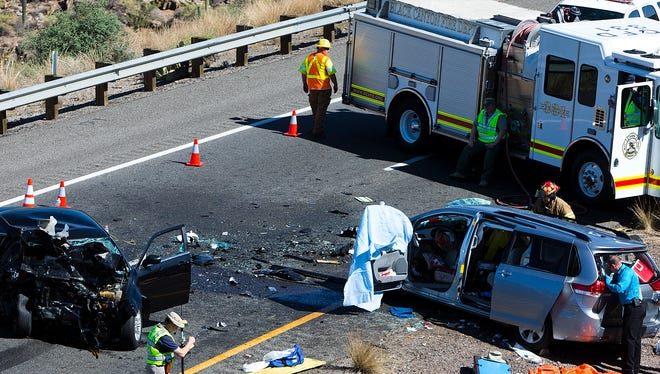 Investigators examine the scene of Friday's wrong-way crash, which left three people dead. The wreck occurred when a Chrysler 300 traveling north on southbound Interstate 17 slammed into a van carrying six people. Police have not identified the Chrysler's driver.