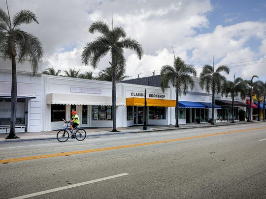 A loan cyclist pedals along S. County Rd. between Royal Palm Way and Brazilian Ave. around 10:15 a.m. that is usually bustling with business at that time, but now due to business closures as a result of the coronavirus, their is very little movement on the street, Tuesday, April 7, 2020.