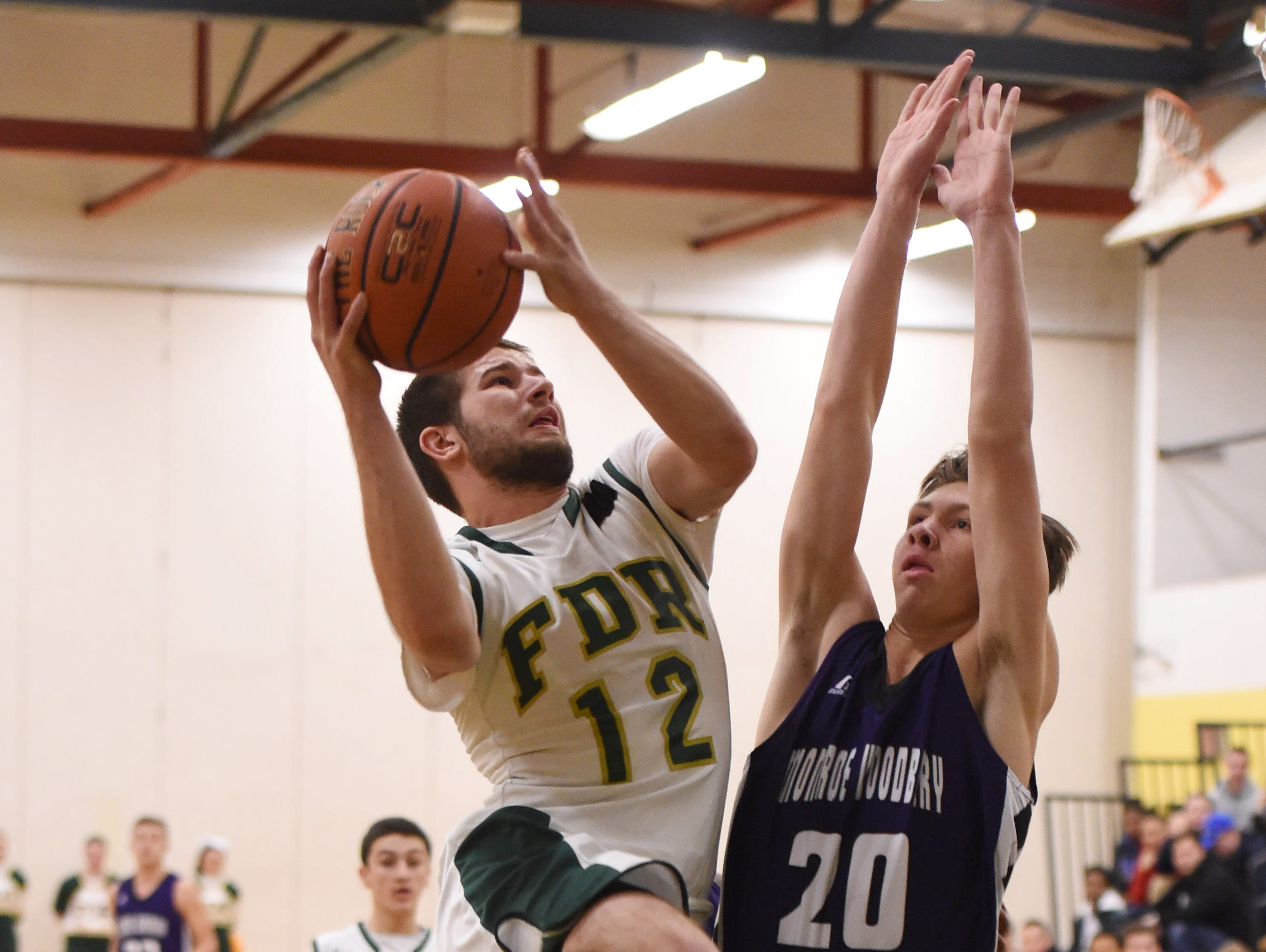 FDR's Aubrey Albertson goes for a layup as Monroe Woodbury's Johnny McCormick defends during Monday's game in Hyde Park.