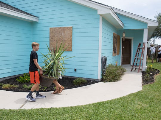 Twelve-year-old Kris Jones and his nine-year-old sister Brooke move plants inside their home on Lighthouse Channel ahead of Hurricane Harvey on Thursday, Aug. 24, 2017.