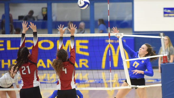Mountain Home's Hope Menendez (right) hits past Vilonia's Gracie James (21) and Gracie Massey (4) during the Lady Bombers' three-set victory Tuesday night at The Hangar.